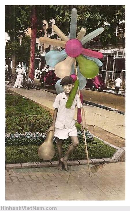 """Một cậu bé bán bóng bay dạo trên phố Sài Gòn cười tươi, """"tạo dáng""""trước ống kính"""