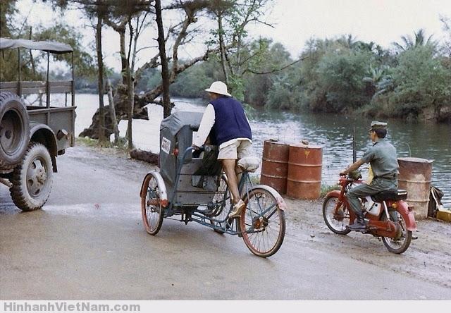 Một người đàn ông đạp xích lô kế bên là người người lính chế độ cũ đi xe máy