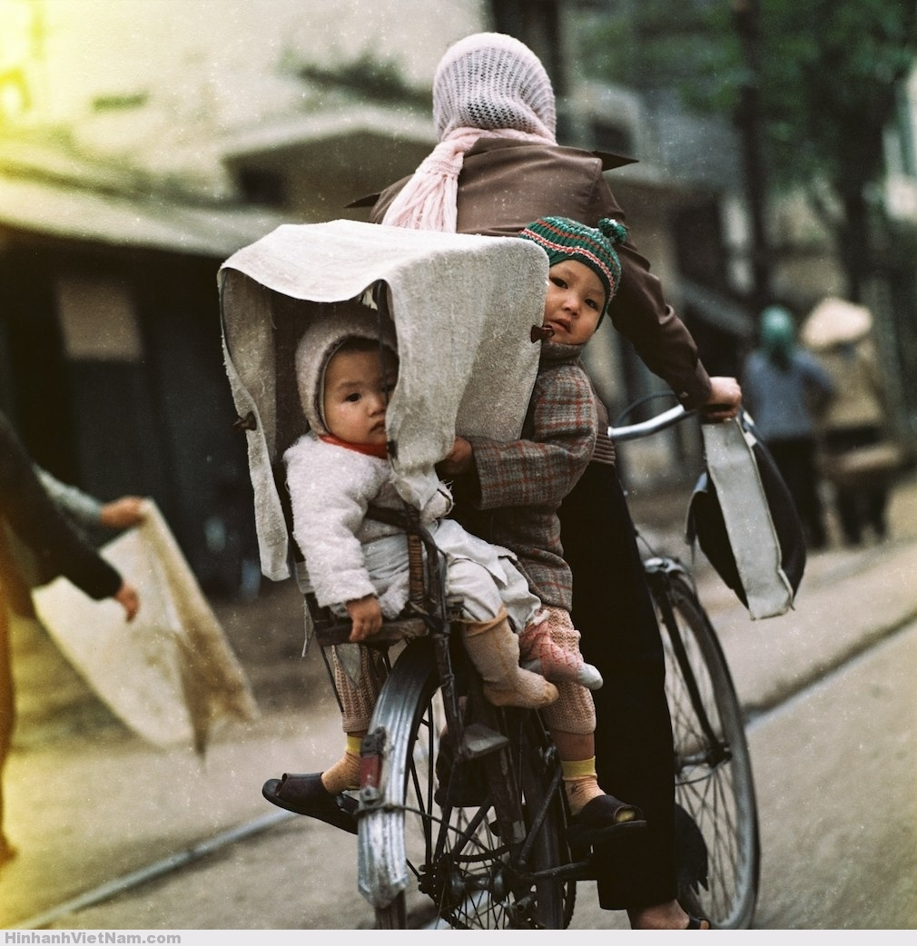 Hai em bé được mẹ chở bằng xe đạp trên phố