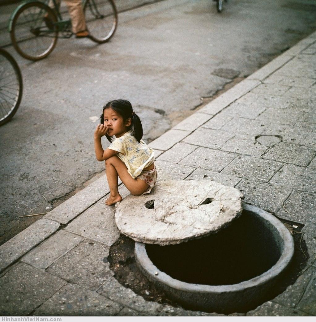 Bé gái ngồi bên miệng hầm trú ẩn.