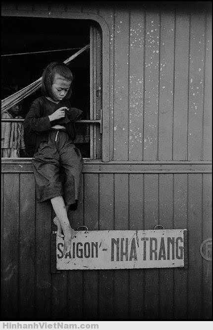 Một bé gái ngồi chấp chới ở cửa sổ một toa tàu.
