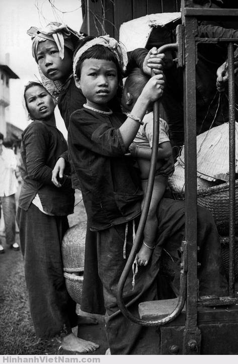 Nhiều đứa trẻ bồng bế nhau theo người lớn lên chuyến tàu đông đúc