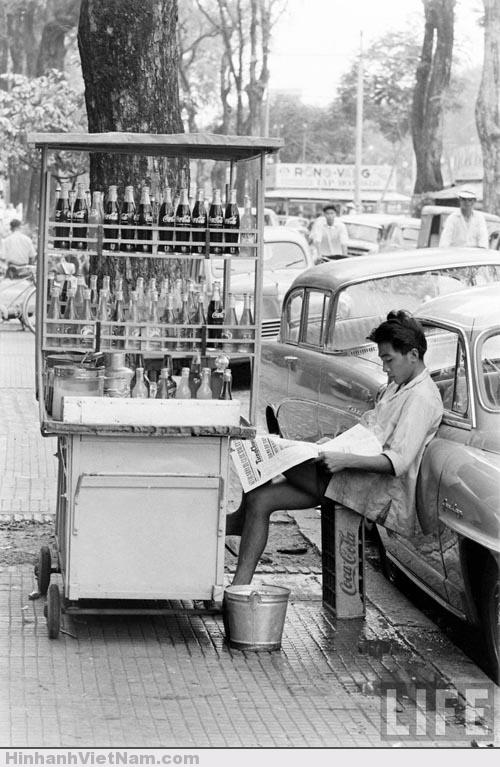 Cậu bé bán nước lấy khay nước ngọt làm ghế ngồi