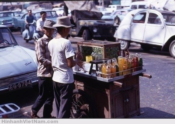 Xe đẩy bán rau má, nước ngọt. Có thể thấy người bán đang chặt đá, kế bên là thanh gỗ để làm đá bào (dành cho món xi rô đá bào mà học sinh rất yêu thích)