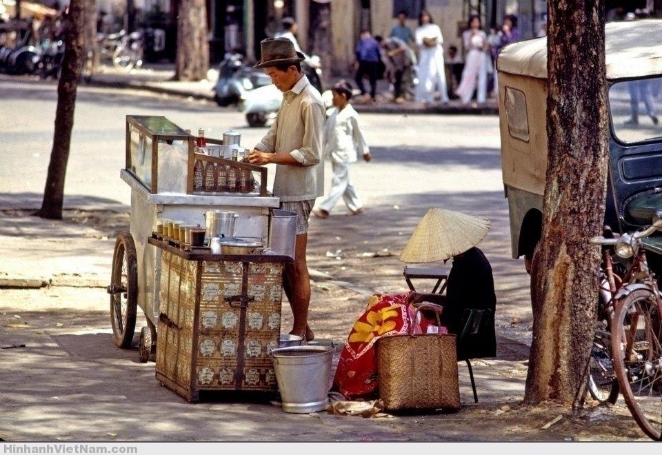Một xe đẩy bán nước bên cạnh một quầy cà phê nhỏ trên vỉa hè Sài Gòn