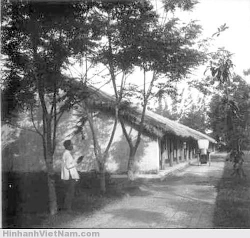 Trường được xây dựng theo kiểu cũ, nhà tranh vách đất, so với ảnh trước cây đã lớn hơn, phía trước lớp học có đường đi sạch sẽ.